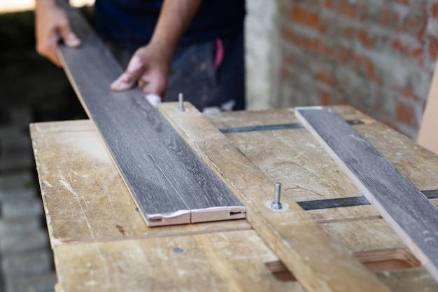 Fabrication et installation de portes. un charpentier coupe une planche de bois sur un tour.