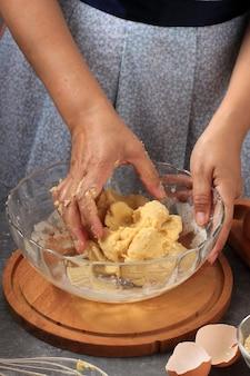 La fabrication de la pâte, une main féminine la préparation de la pâte à pain dans un bol transparent dans la cuisine