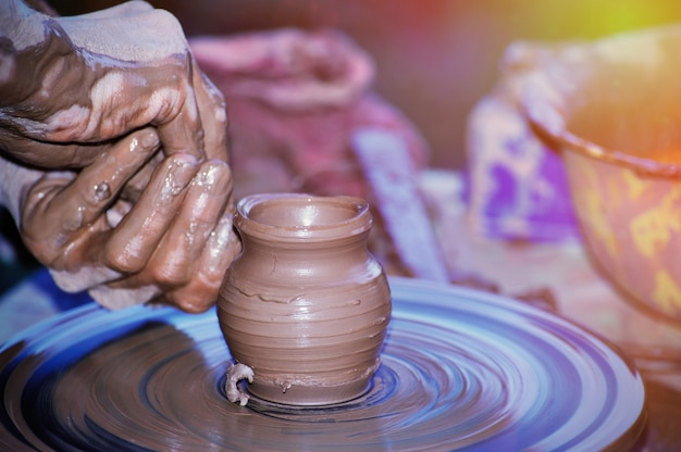 Fabrication de poterie traditionnelle, gros plan sur les mains du potier façonnant un bol