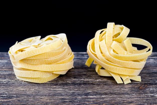 Fabriqué à partir de pâtes à la farine de blé, blé dur, gros plan dans la cuisine avant la cuisson des pâtes crues