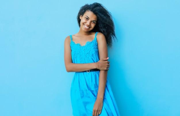 Une fabuleuse fille afro-américaine rit de joie et regarde dans la caméra tout en posant avec sa main gauche pliée et sa main droite pliée