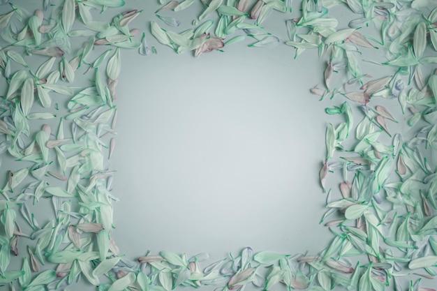 Fabuleux cadre carré printemps été avec des pétales de fleurs dans des tons verts, sur un fond mat crème rose rosé.