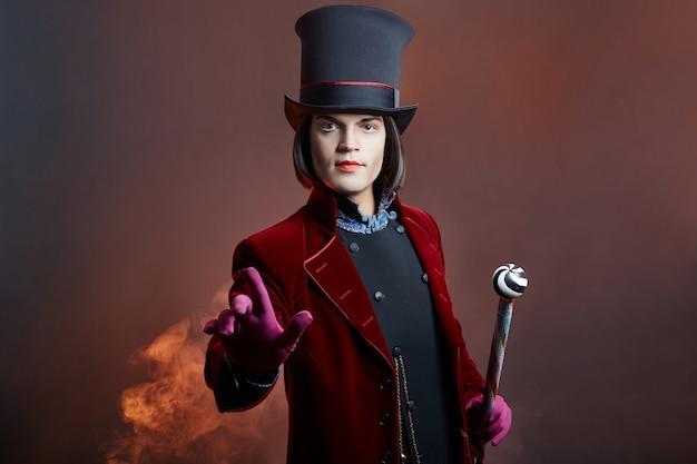 Fabuleux homme de cirque avec un chapeau et un costume rouge posant dans la fumée