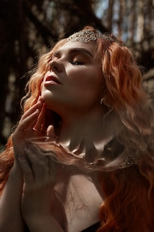Fabuleux portrait d'une fille rousse dans la nature avec double exposition et éblouissement. belle fille rousse aux cheveux longs dans la forêt, regard mystérieux et grands yeux, feuilles et herbe sur son visage