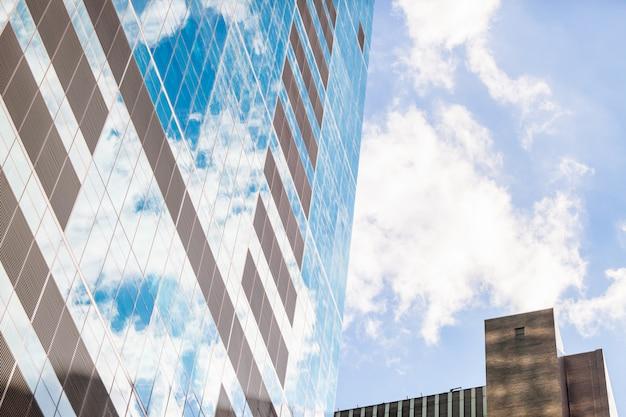 Façade abstraite d'un gratte-ciel moderne avec des nuages réfléchis