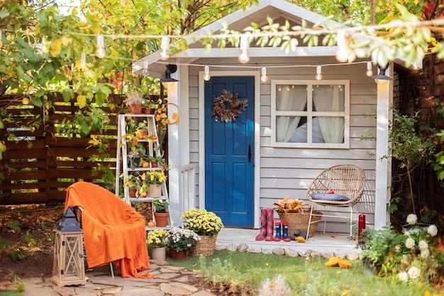 Façade automne maison confortable avec porche avec chaise, couverture, chrysanthèmes.