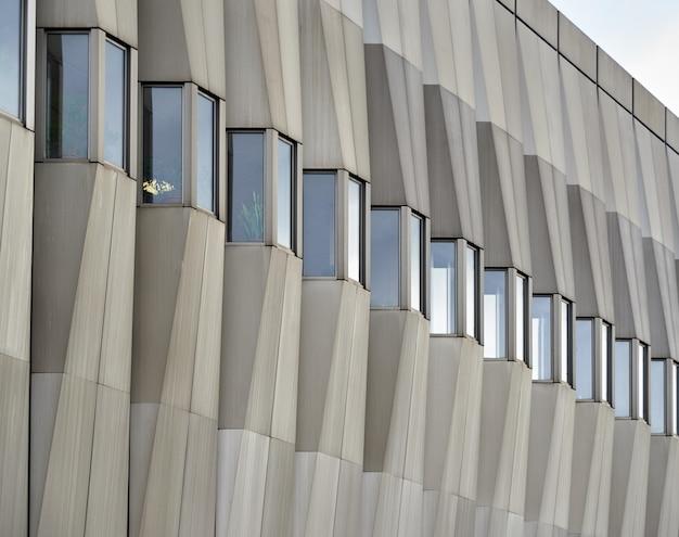 Façade d'un bâtiment moderne en béton avec de petites fenêtres par temps nuageux