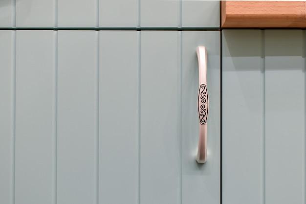 Façade bleu clair de l'armoire de cuisine avec des poignées gracieuses. partie du gros plan intérieur de la cuisine moderne.
