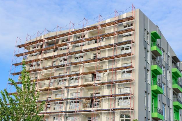 Façade du bâtiment en construction avec des échafaudages contre le ciel bleu