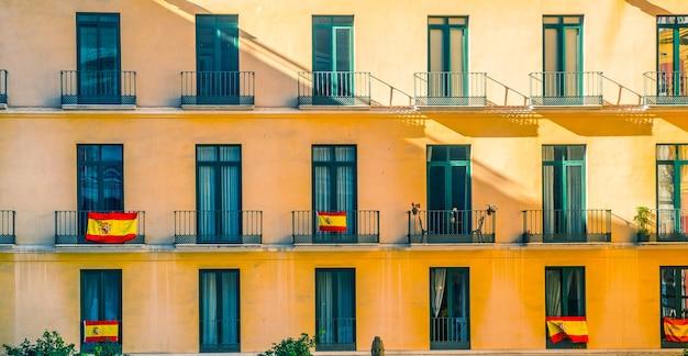 Façade avec fenêtres et drapeaux espagnols.