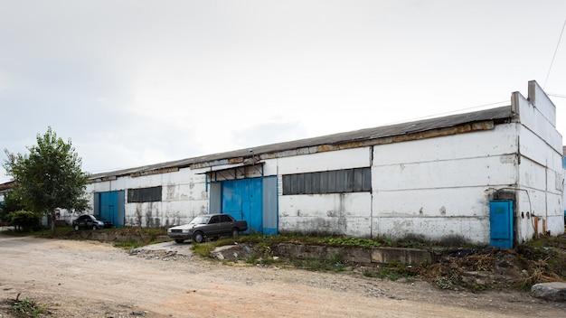Façade d'un grand bâtiment industriel constitué de panneaux métalliques blancs et bleus.