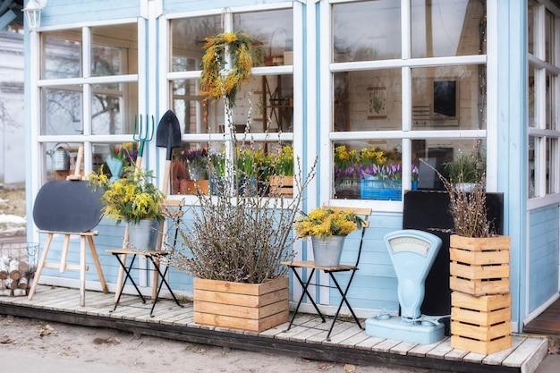 Façade maison avec outils de jardin pots de fleurs véranda d'été confortable porche en bois de maison avec plantes et branches mimosa jaune