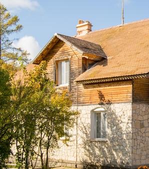 La façade d'une maison en pierre à deux étages avec un grenier et un toit de tuiles brunes.