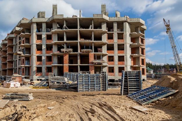 Façades d'un immeuble de plusieurs étages en construction outils de chantier brouette sable un
