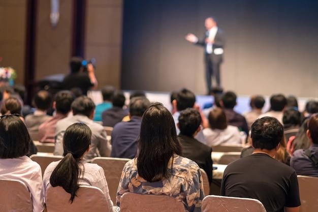 Face arrière des audiences assis et écoutant les interlocuteurs sur la scène