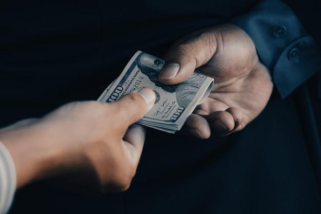 Face arrière d'un homme d'affaires qui offre un pot-de-vin à des représentants du gouvernement concept de corruption