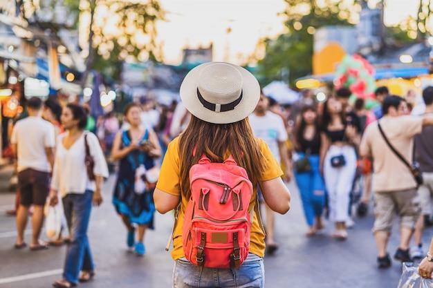 Face arrière de jeunes femmes asiatiques voyageant à pied et à la recherche à chatujak week-end marche marché de rue en soirée à bangkok