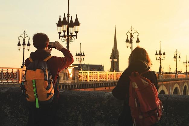 Face arrière des touristes prenant des photos du pont de pierre pont de pierre à bordeaux, france