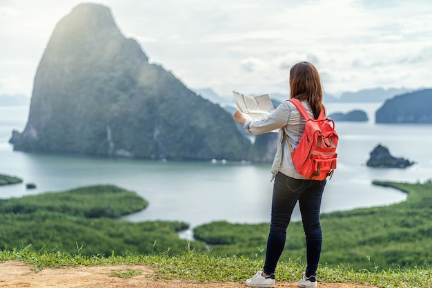 Face arrière d'un voyageur asiatique regardant la carte pour voyager avec un routard chez fantastic