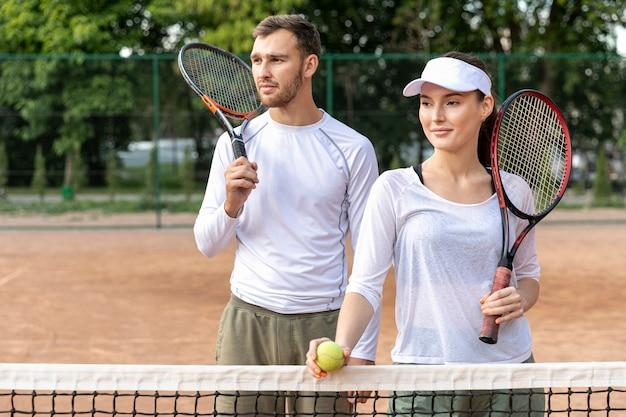 Face couple heureux sur le court de tennis