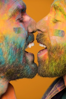 Face à face des hommes homosexuels heureux dans la peinture arc en ciel