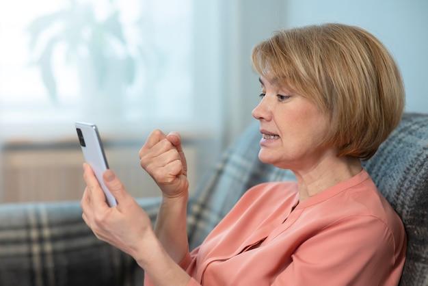 Fâché agressif furieux irrité femme, personnes âgées senior adult lady agite son poing sur l'écran de