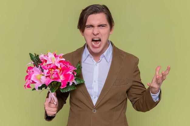 Fâché en colère jeune homme fou tenant un bouquet de fleurs à l'avant en criant va sauvage journée internationale de la femme debout sur le mur vert