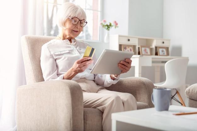 Facile et pratique. adorable femme âgée assise dans le fauteuil confortable et faire des achats en ligne, prête à payer avec sa carte de crédit