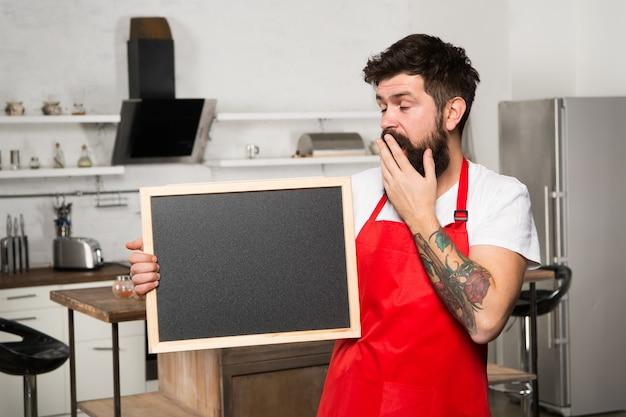Des façons intelligentes d'organiser la cuisine. cook tenir l'espace de copie de tableau vierge. conseils secrets. informations utiles. tablier rouge hipster barbu homme stand dans la cuisine. magasin de meubles de cuisine. concept de hacks de cuisine.