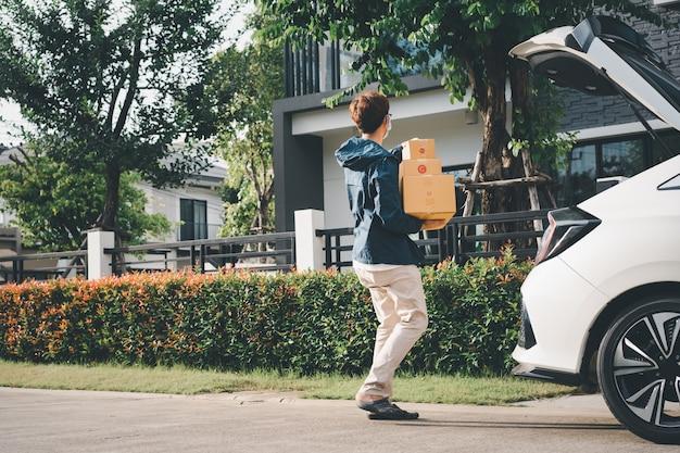 Facteur asiatique avec un masque facial de protection de l'hygiène ramasser un colis