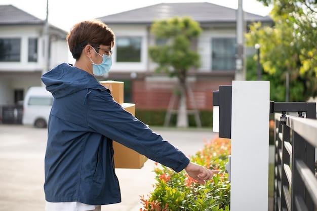 Facteur asiatique avec un masque protecteur d'hygiène ramassant un colis ou une boîte à colis. nouveau concept normal pendant la pandémie de covid-19 ou de coronavirus