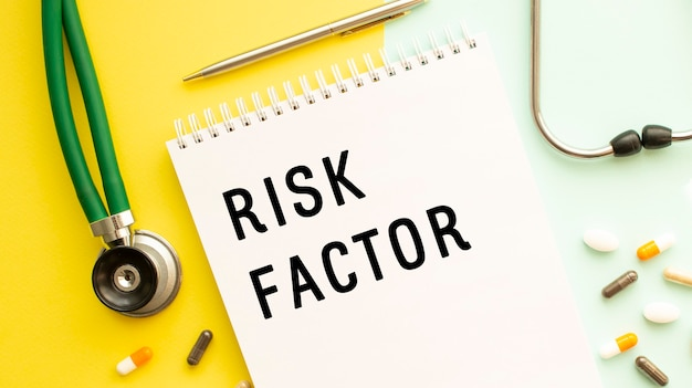 Facteur de risque est écrit dans un cahier sur une table à côté de pilules et d'un stéthoscope