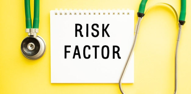 Facteur de risque de texte sur ordinateur portable avec stéthoscope sur surface jaune