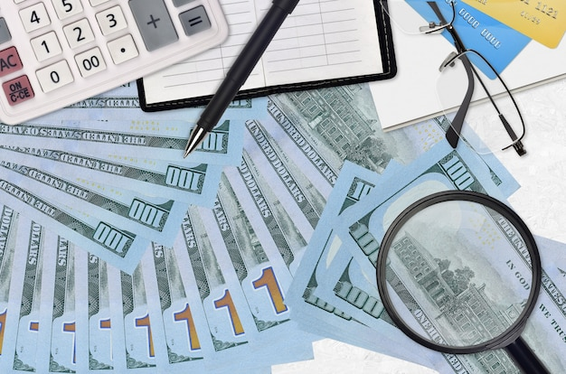Factures de 100 dollars américains et calculatrice avec lunettes et stylo. concept de saison de paiement des impôts ou solutions d'investissement. rechercher un emploi avec un salaire élevé