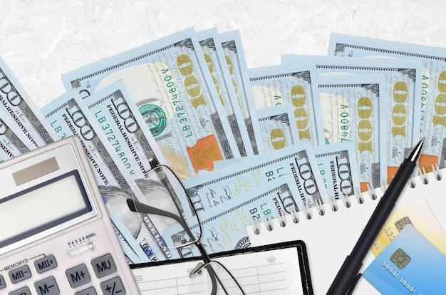 Factures de 100 dollars américains et calculatrice avec lunettes et stylo