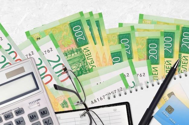 Factures de 200 roubles russes et calculatrice avec lunettes et stylo. concept de paiement d'impôt ou solutions d'investissement. planification financière ou paperasse comptable