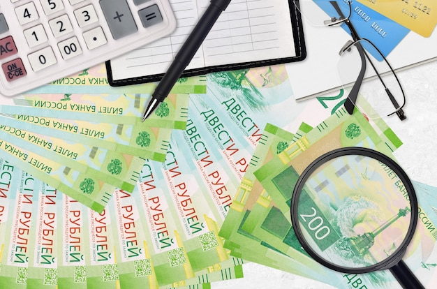 Factures de 200 roubles russes et calculatrice avec lunettes et stylo.