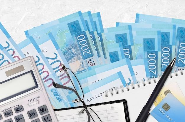 Factures de 2000 roubles russes et calculatrice avec lunettes et stylo. concept de saison de paiement des impôts ou solutions d'investissement. planification financière ou paperasse comptable