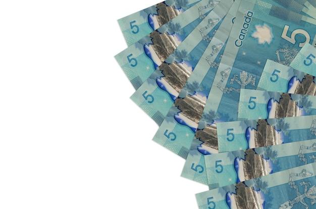 Les factures de 5 dollars canadiens se trouvent isolés sur un mur blanc avec espace de copie. mur conceptuel de vie riche. grande quantité de richesse en monnaie nationale