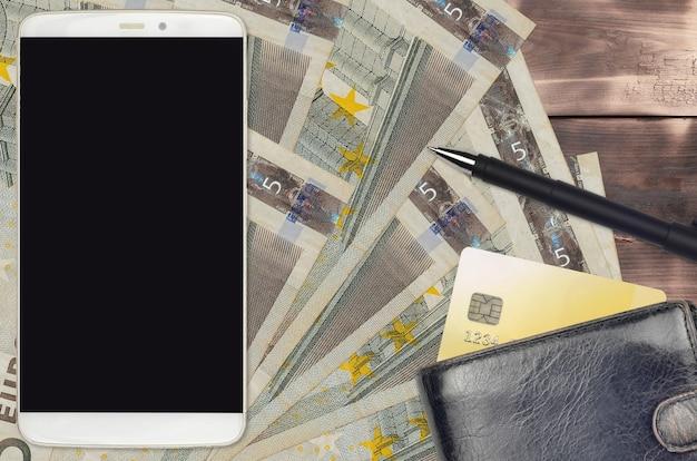 Factures de 5 euros et smartphone avec sac à main et carte de crédit.