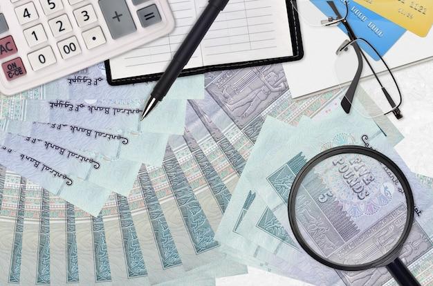 Factures de 5 livres égyptiennes et calculatrice avec lunettes et stylo. concept de saison de paiement des impôts ou solutions d'investissement.