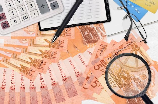 Factures de 5 roubles biélorusses et calculatrice avec lunettes et stylo. concept de saison de paiement des impôts ou solutions d'investissement. rechercher un emploi avec un salaire élevé