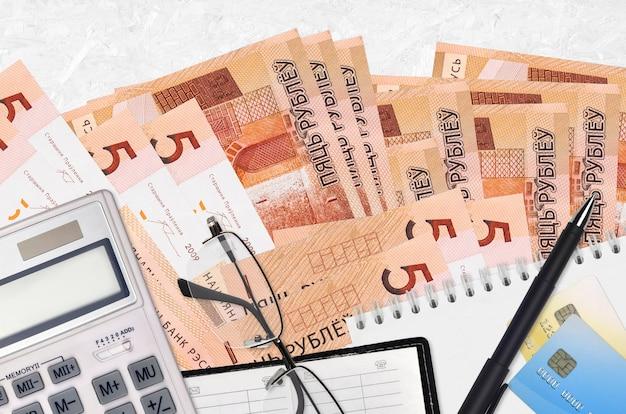 Factures de 5 roubles biélorusses et calculatrice avec lunettes et stylo