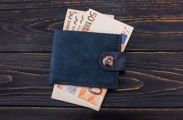 Factures de 50 euros dans le portefeuille d'un homme sur un fond en bois. fermer.