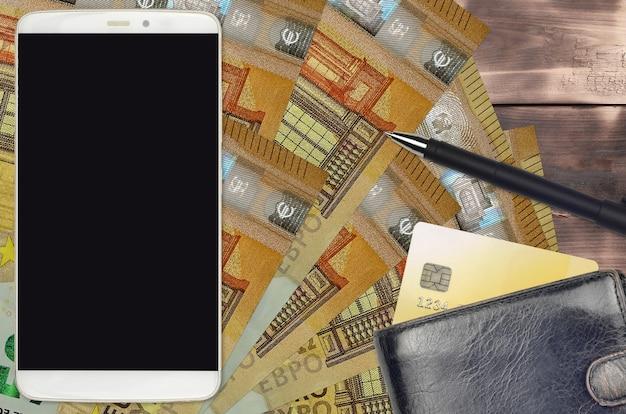 Factures de 50 euros et smartphone avec sac à main et carte de crédit