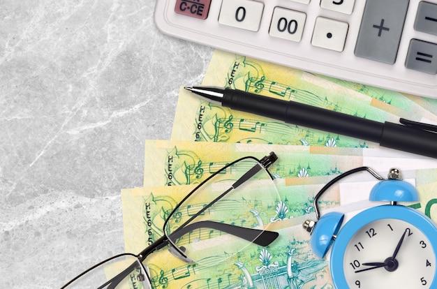 Factures de 50 roubles biélorusses et calculatrice avec lunettes et stylo. prêt commercial ou concept de saison de paiement des impôts. il est temps de payer les impôts