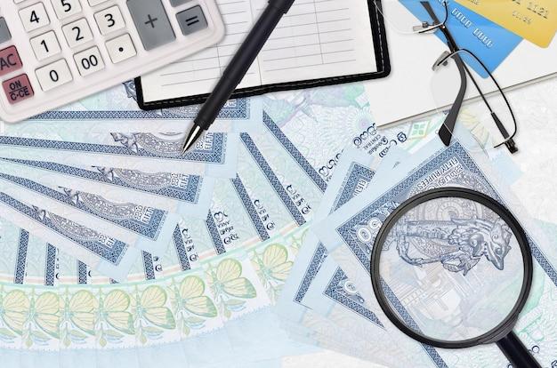 Factures de 50 roupies sri-lankaises et calculatrice avec lunettes et stylo. concept de saison de paiement des impôts ou solutions d'investissement. rechercher un emploi avec un salaire élevé