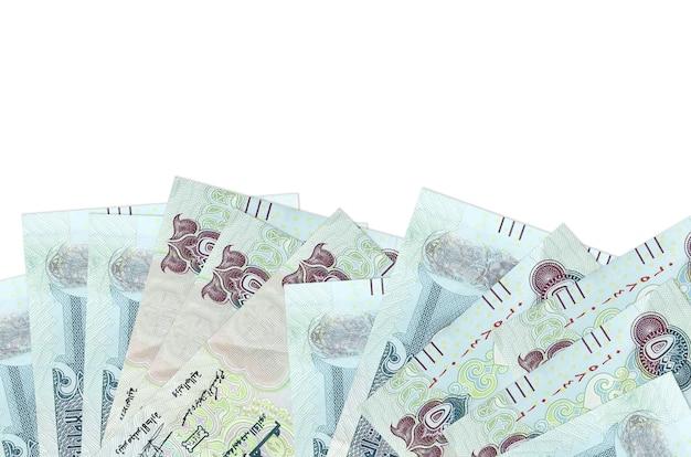 Les factures de 500 dirhams des émirats arabes unis se trouvent sur la face inférieure de l'écran isolé sur un mur blanc avec copie espace.