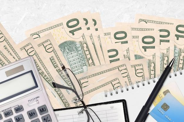 Factures en dollars américains et calculatrice avec lunettes et stylo