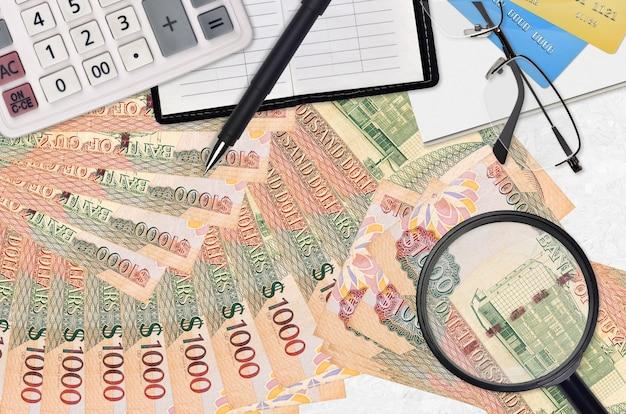 Factures en dollars guyanais et calculatrice avec lunettes et stylo